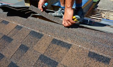 bitumen dakbedekker aan het dakdekken