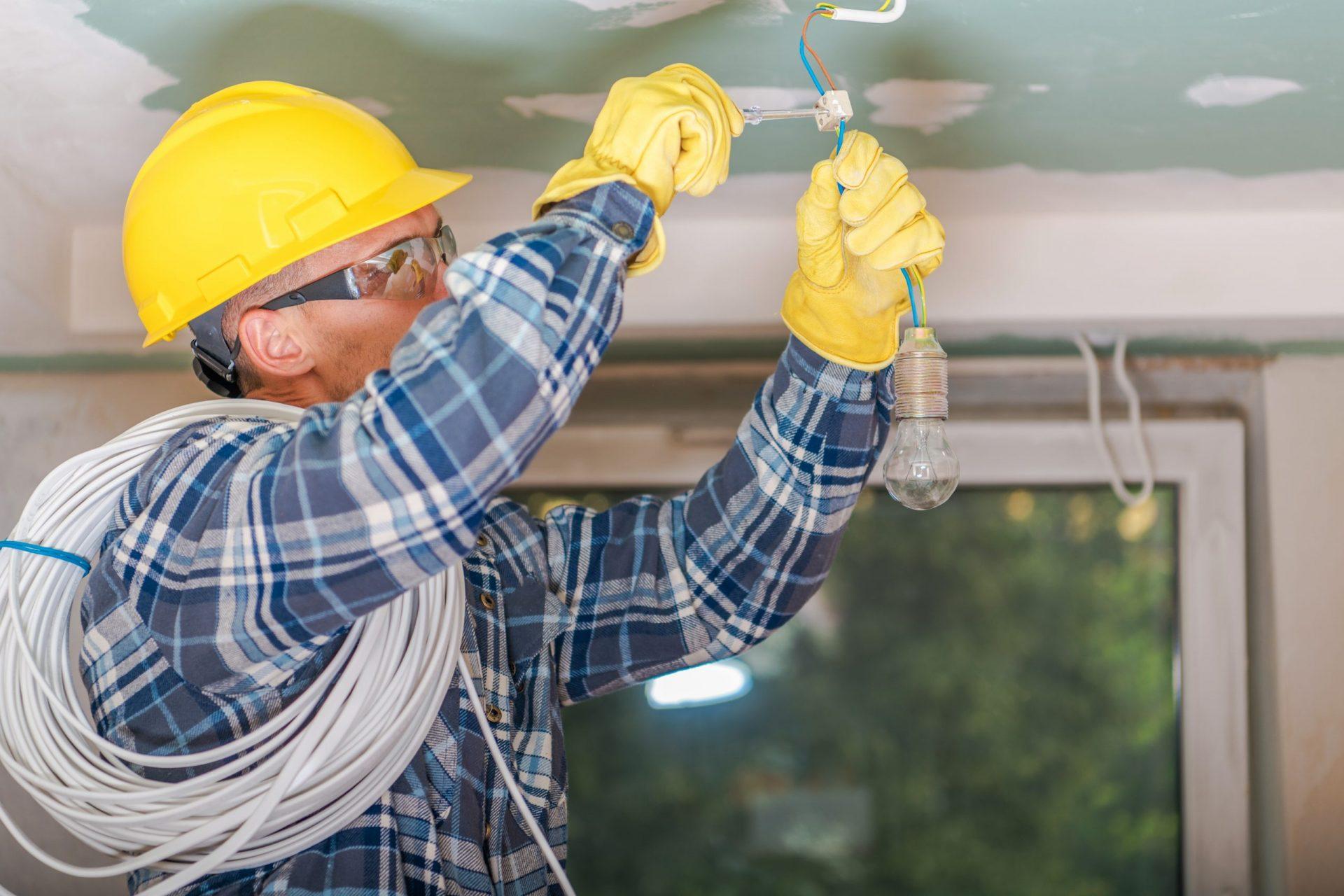 Monteur lampen aan het ophangen